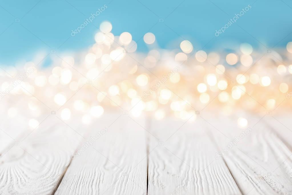 bright blurred lights on white wooden surface, christmas texture
