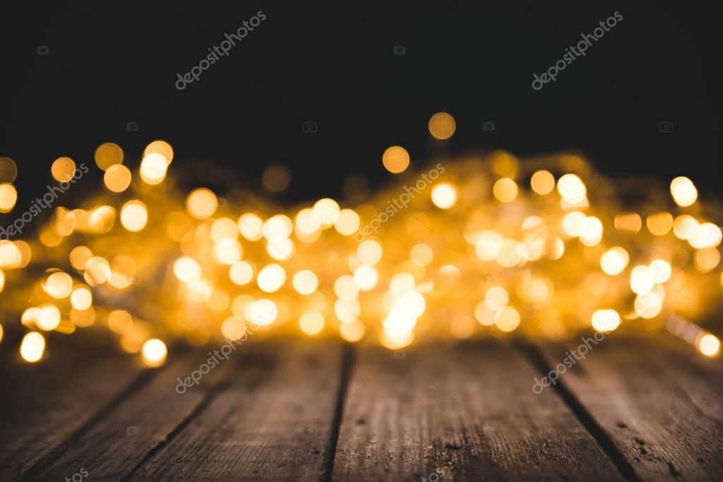 christmas bokeh lights on wooden surface