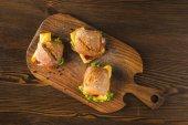 pohled shora tři chleby se sýrem a zeleninou na dřevěné desce