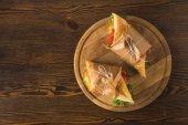 vista superiore di due deliziosi panini sul tagliere sulla tavola di legno