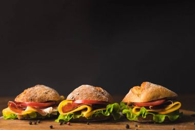 sandwiches with cheese and vegetables on wooden board with scattered pepper