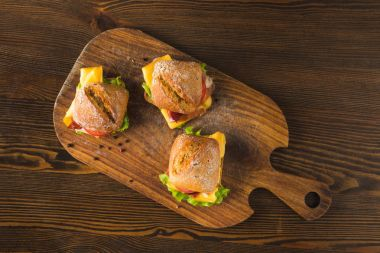 top view of three sandwiches with cheese and vegetables on wooden board