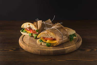 two cooked delicious panini with vegetables on wooden board