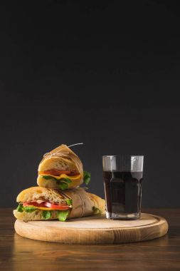 two sandwiches on each other and glass of cola on cutting board