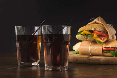 two glasses of cola on table and panini on wooden board