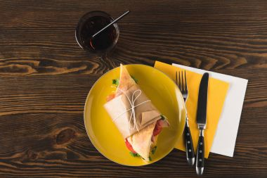 top view of panini on yellow plate with fork and knife on napkins
