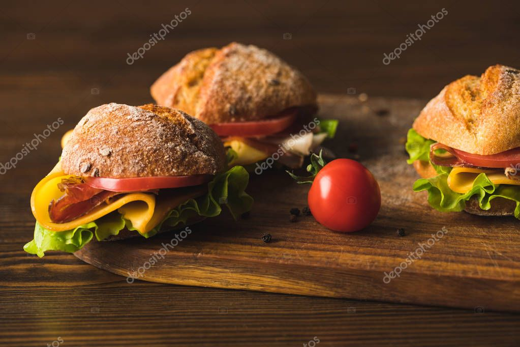 sandwiches with cheese and cherry tomato on cutting board