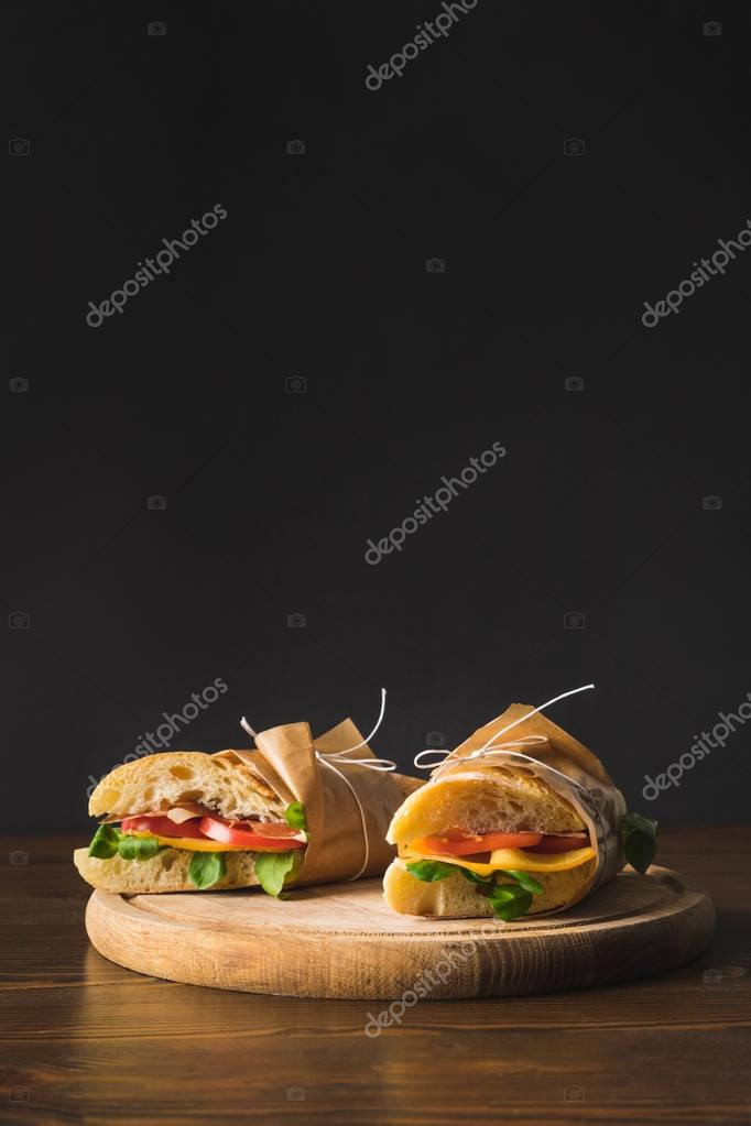 two cooked appetizing sandwiches with vegetables on cutting board