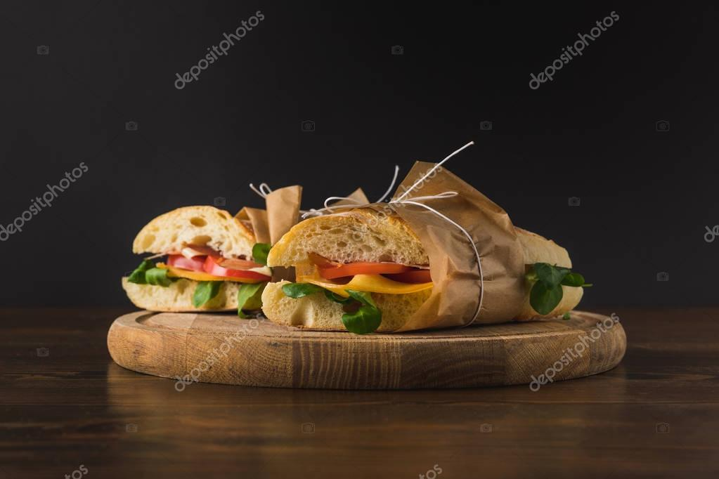 two cooked appetizing sandwiches with vegetables on wooden board