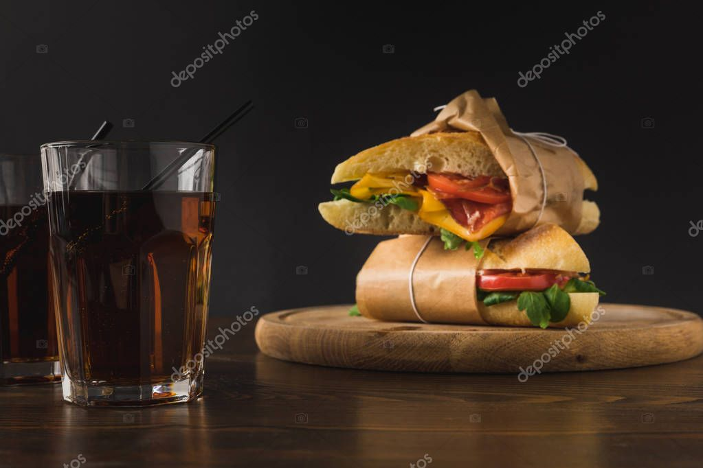 two sandwiches on each other on wooden board