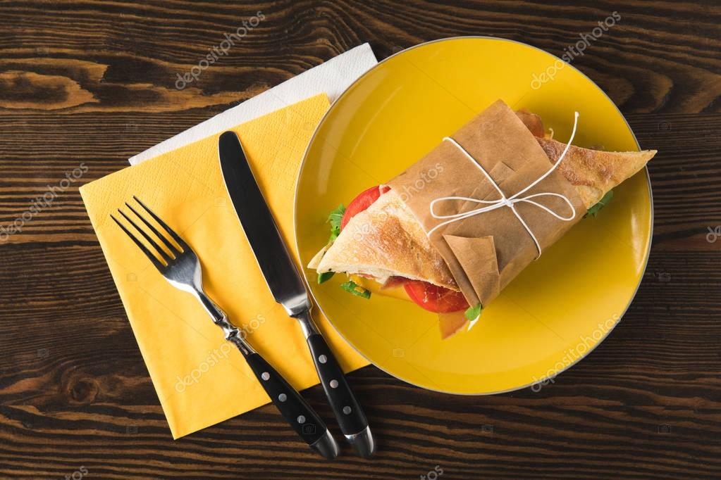 top view of panini on yellow plate with fork and knife