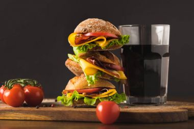 big sandwich with cherry tomatoes and glass of cola on cutting board