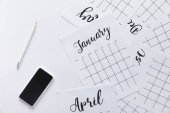 Photo flat lay with calendar, smartphone and pencil isolated on white