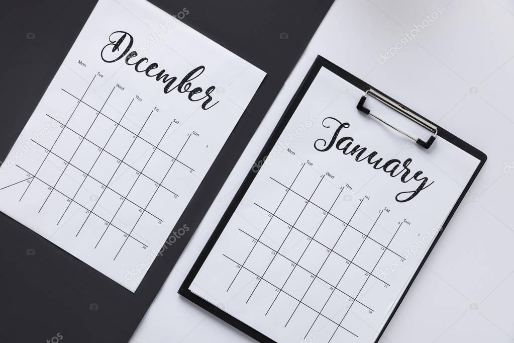 top view of notepad and calendar on black and white surfaces