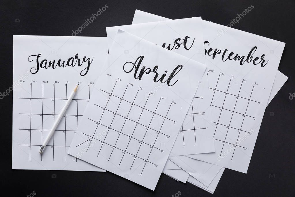 flat lay with paper calendar and pencil isolated on black
