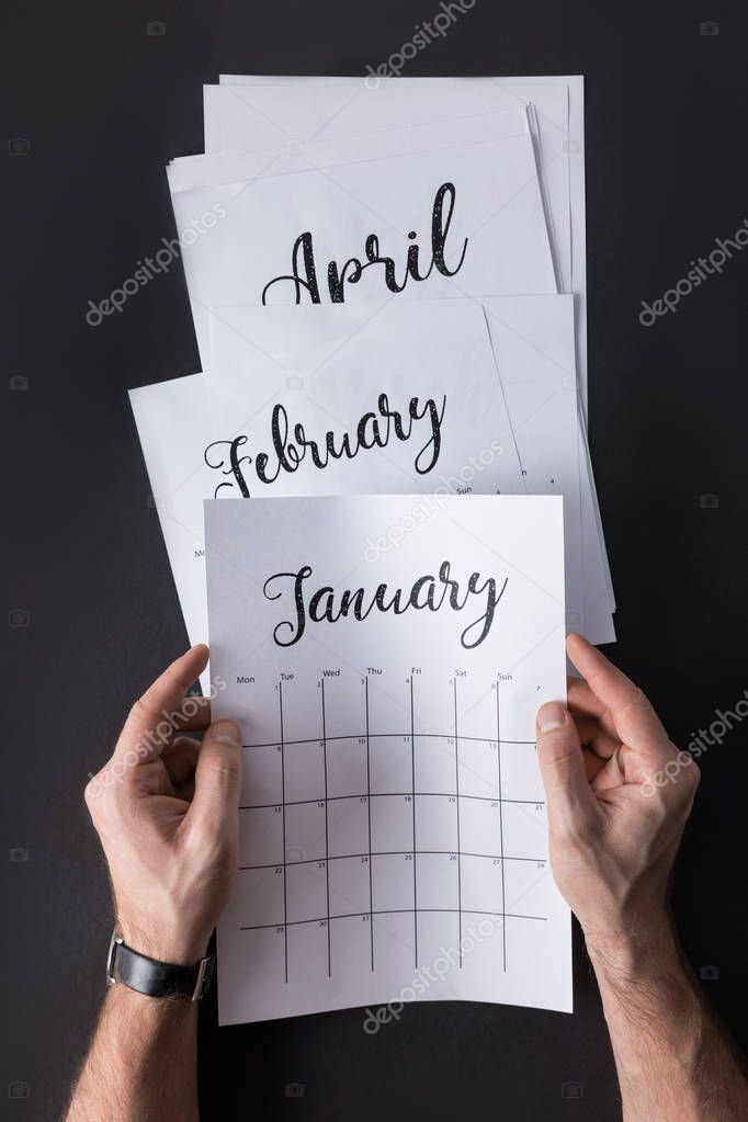 partial view of man holding calendar in hands isolated on black