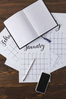 flat lay with empty notebook, calendar, pencil and smartphone on wooden surface