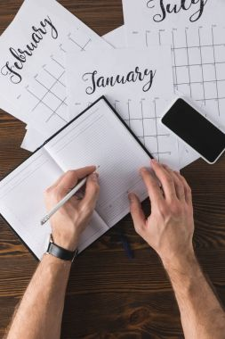 partial view of businessman making notes in notebook at table with calendar