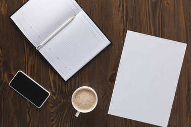 flat lay with smartphone, notebook, pencil and cup of coffee on wooden tabletop