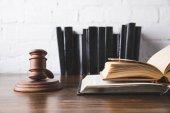 Libri giuridici aperti con il martelletto sulla tavola di legno, concetto di legge