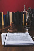 juridical contract on wooden table with hammer and lady justice, law concept