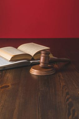 opened juridical books with hammer on wooden table, law concept