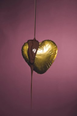 heart shaped candy in golden wrapper with pouring liquid chocolate isolated on pink