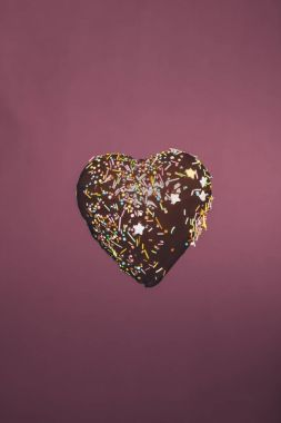 chocolate heart shaped candy with glaze isolated on pink
