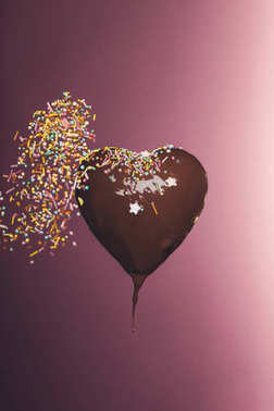 chocolate heart shaped candy with falling glaze isolated on pink