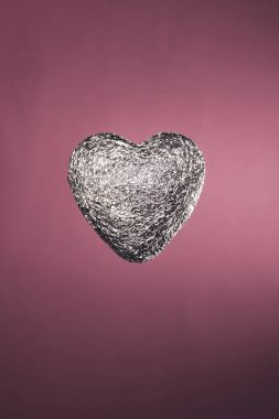 heart shaped candy in silver wrapper isolated on pink