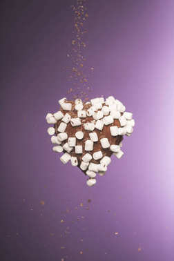 chocolate heart shaped candy with marshmallow and falling crumbled chocolate isolated on purple
