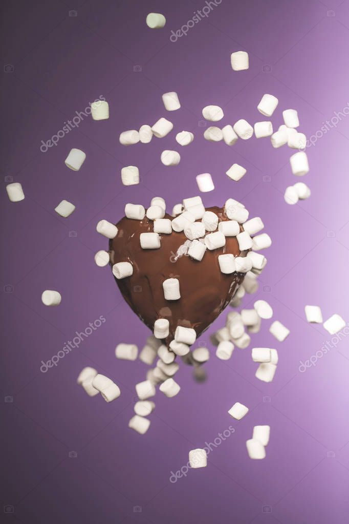 heart shaped chocolate candy with falling marshmallow isolated on purple