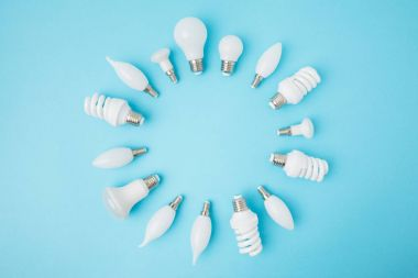 top view of different white lamps arranged in circle isolated on blue