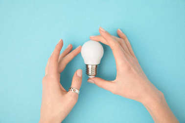 partial view of woman holding light bulb in hands isolated on blue