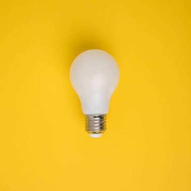 close up view of white light bulb isolated on yellow
