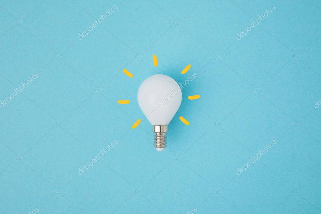 close up view of white light bulb with yellow lines isolated on blue