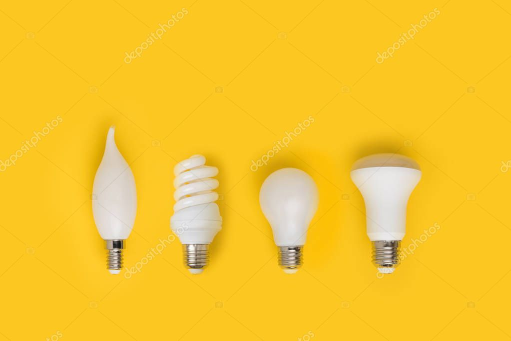 top view of set of different white lamps isolated on yellow