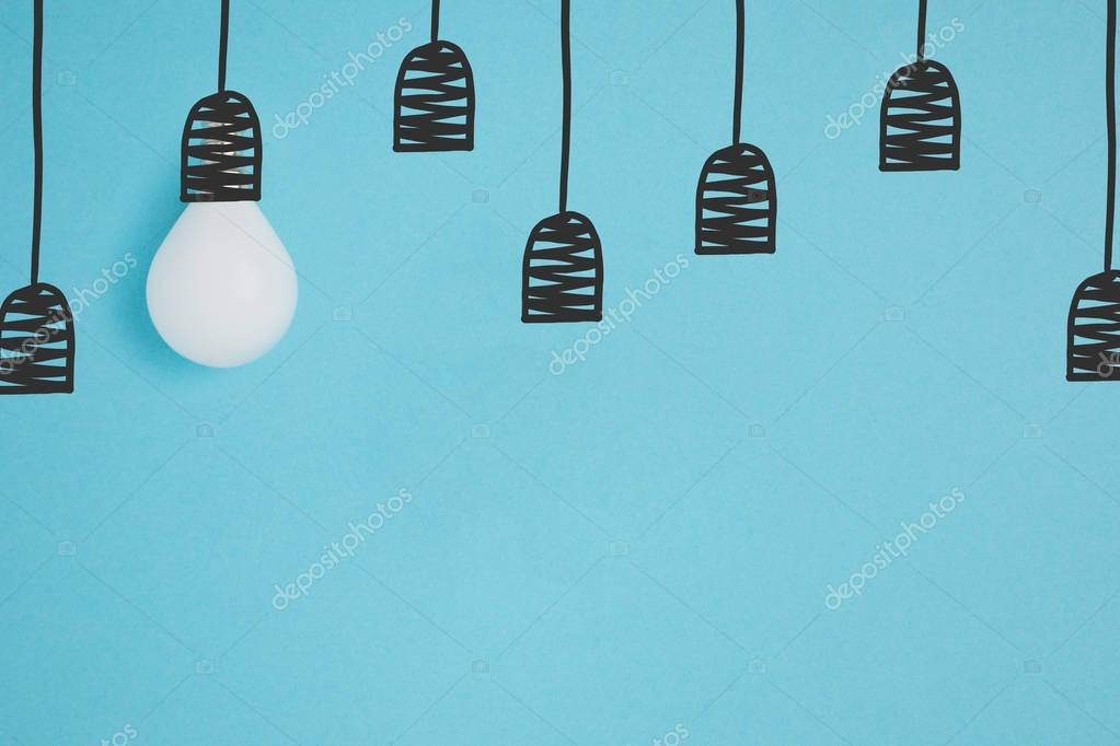 flat lay with white light bulb pretending hanging on string isolated on blue