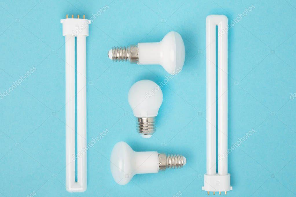 flat lay with arranged various light bulbs isolated on blue