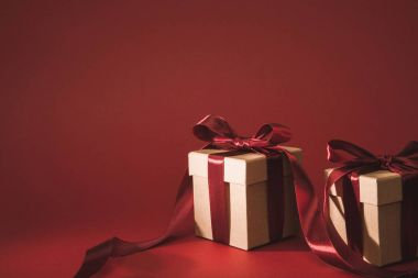 close up view of three gift boxes decorated with ribbons on red