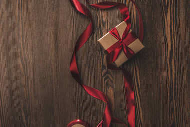 Flat lay with present and red ribbon on wooden tabletop stock vector