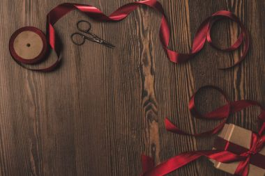 flat lay with arranged red ribbon, present and scissors on wooden surface