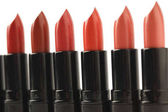 close-up shot of row of red lipsticks of various shades isolated on white