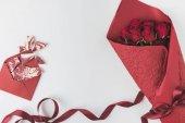 Fotografie plochý ležel s uspořádáním kytice červených růží s pásu a obálku s sladký dezert izolované na bílém, st valentines day koncept
