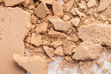 top view of spilled nude cosmetic powder as background