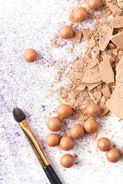 top view of crushed cosmetic powder with brush on white table