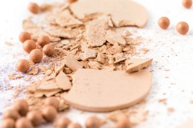 close-up shot of spilled cosmetic powder on white surface