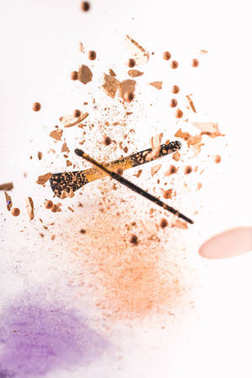 crushed cosmetic powder with makeup brushes falling isolated on white