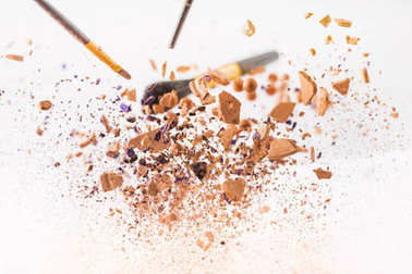 close-up shot of pieces of cosmetic powder with makeup brushes falling isolated on white