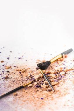 makeup brushes lying on white surface spilled with cosmetic powder